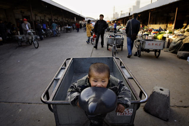 Drengur í reiðhjólakerru á markaði í Peking.