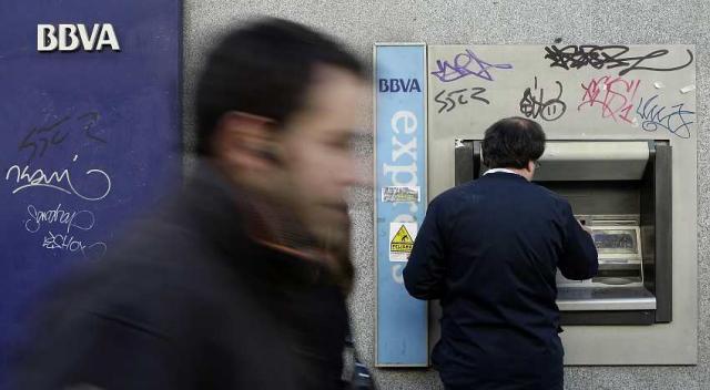 Spánverji tekur evrur út úr hraðbanka í Madrid.
