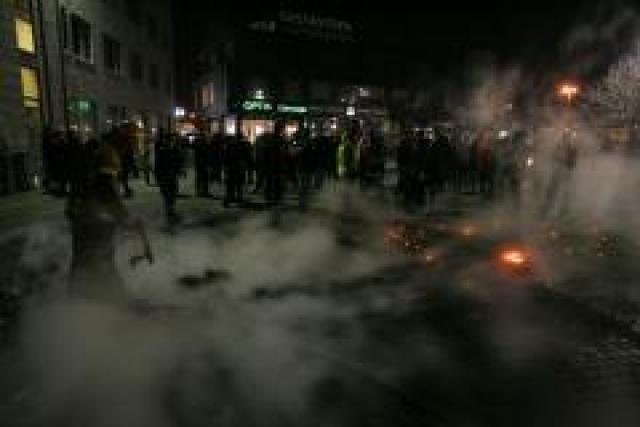 Slökkviliðsmenn slökkva eld sem kveiktur var á Lækjartorgi.