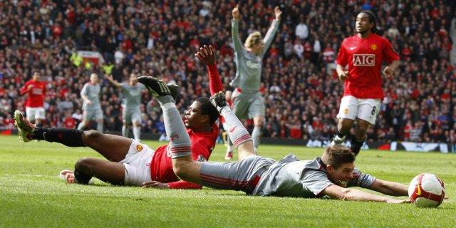 Steven Gerrard liggur í teignum eftir brot Patrice Evra.