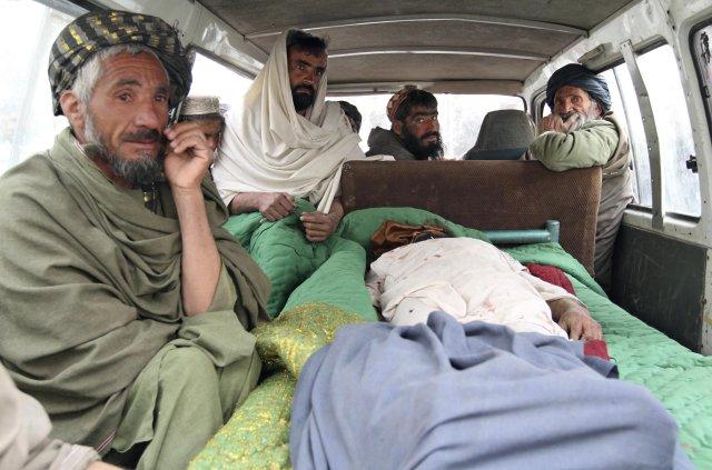 Afganskir menn í rútu þar sem lík eins fórnarlamba hermannsins ...