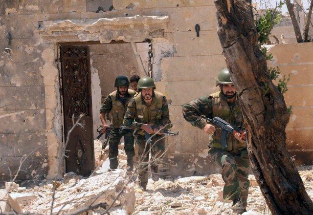 Hermenn stjórnarhersins í húsarústum þorpsins Dahret Abed Rabbo nærri Aleppo.