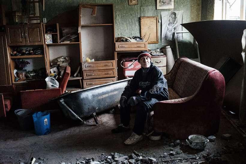 Maður situr í rústum íbúðar sinnar í Donetsk í apríl ...