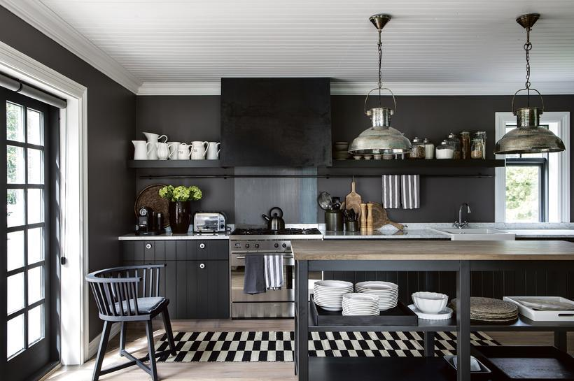 A kitchen painted in a dark shade of grey with ...