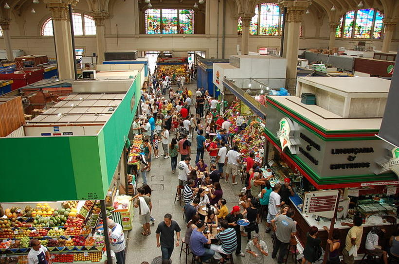 People shopping and munching at a food Market in São ...
