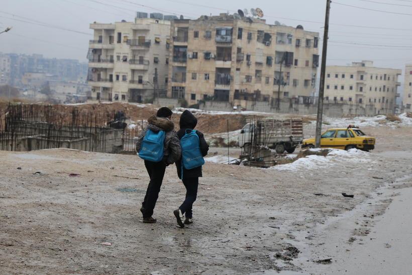 Sýrlenskir drengir ganga í Aleppo.