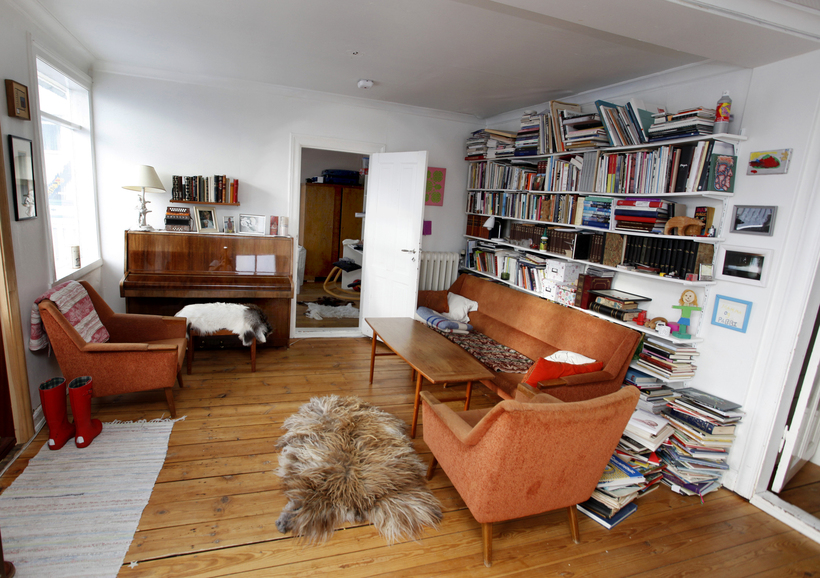 The living room features plenty of books, warm hued furniture ...