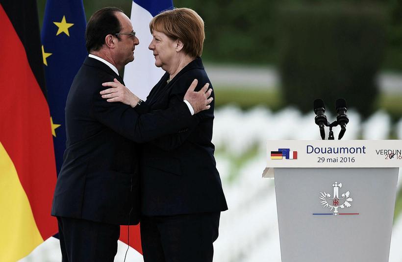 Merkel og Hollande fallast í faðma við athöfnina í dag.