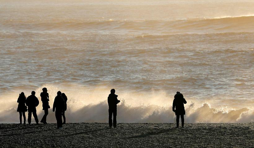 Tourists playing in the waves at Reynisfjara beach yesterday.