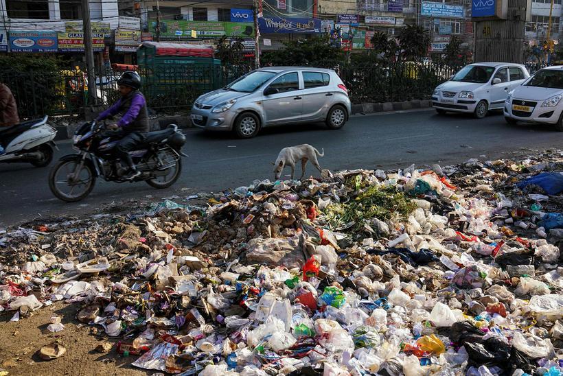 Indverskir vegfarendur fara framhjá ruslahaug í Nýju Delhi.