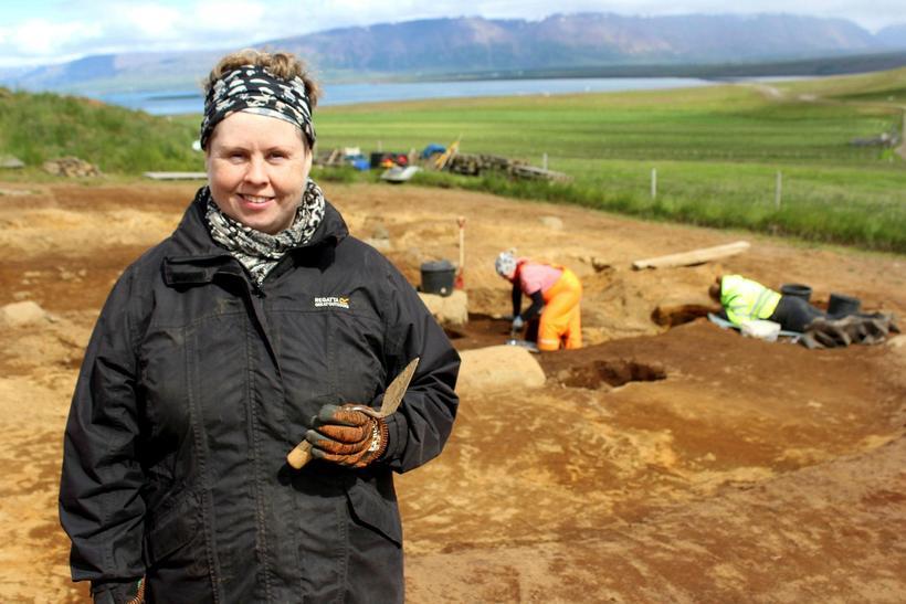 Guðný Zoëga með þarfaþingið múrskeiðina og kirkjugarð, vettvang rannsóknar, í ...