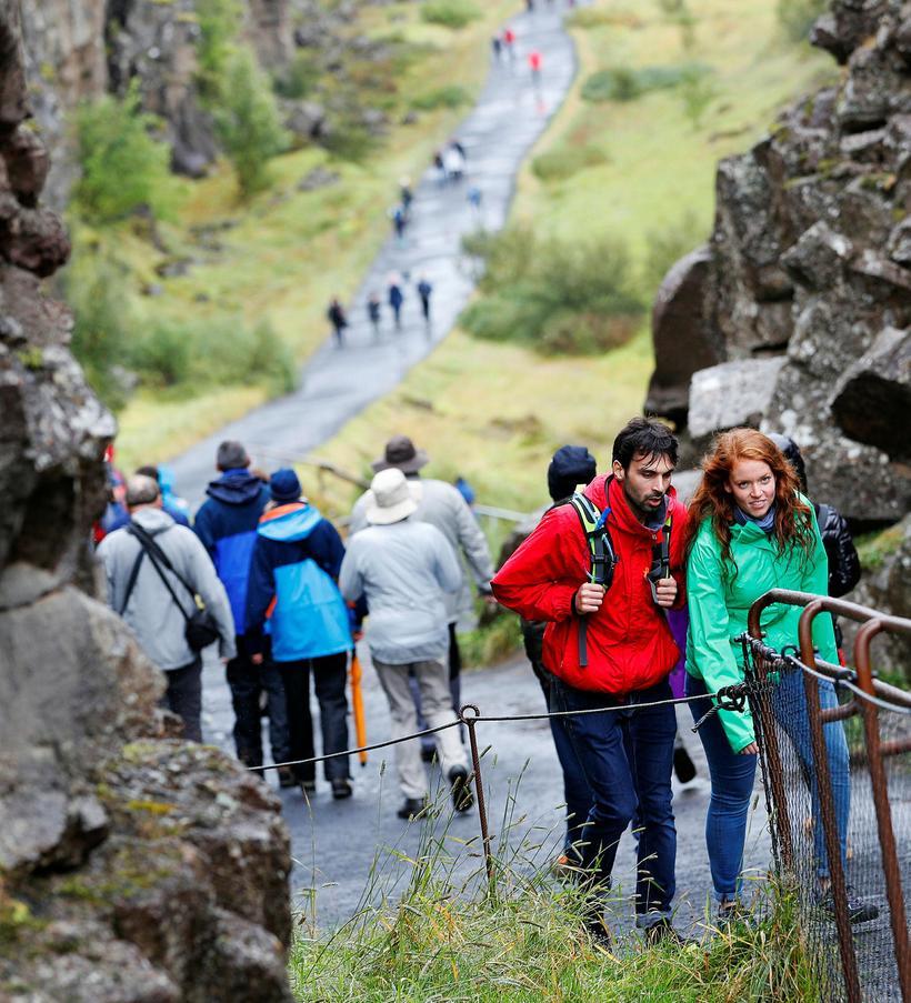 Tourists walking in Almannagjá, a famous crevasse.
