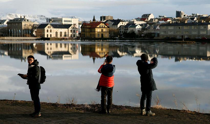 Ferðamenn við spegilslétta Reykjavíkurtjörn.
