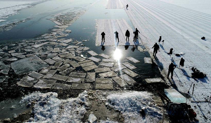 Ís skorinn í kubba fyrir ferðamenn á Xiuh-vatni í Kína.