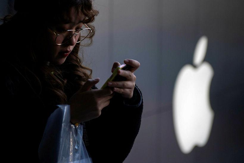 Kínversk kona handfjatlar iPhone-síma fyrir utan Apple-búð í Peking í ...