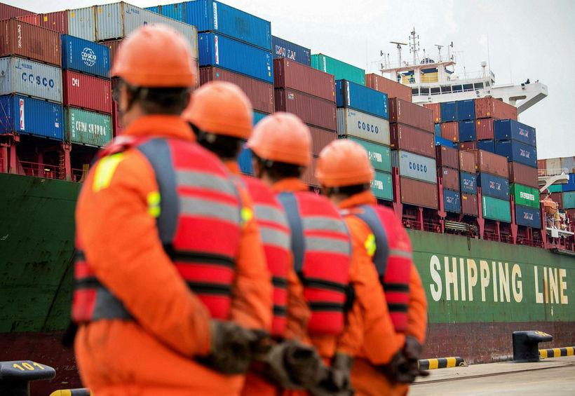 Hafnarstarfsmenn í Qingdao í austurhluta Kína fylgjast með flutningaskipi við ...