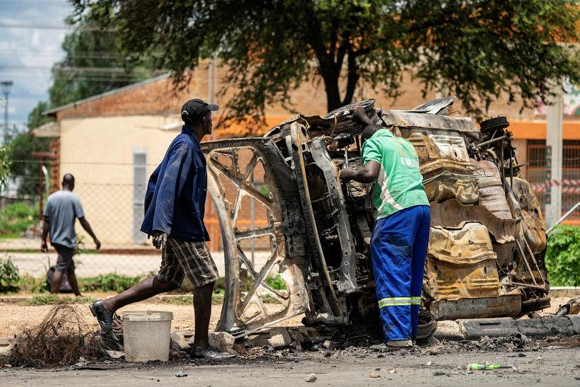 Menn safna brotajárni úr brenndum bíl í borginni Bulawayo í ...
