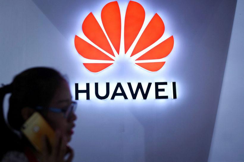 Kona notar síma sinn við merki Huawei í Peking. Meng ...