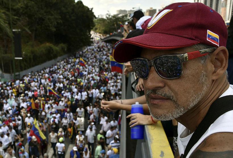 Stuðningsmenn Juan Guaidó taka hér þátt í mótmælagöngu í Caracas ...