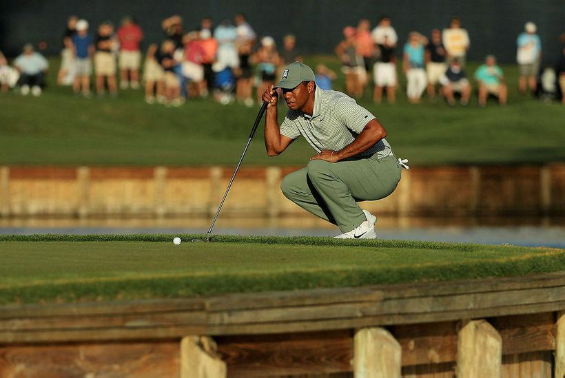 Tiger Woods skoðar púttlínuna á 17. flötinni þar sem hann ...
