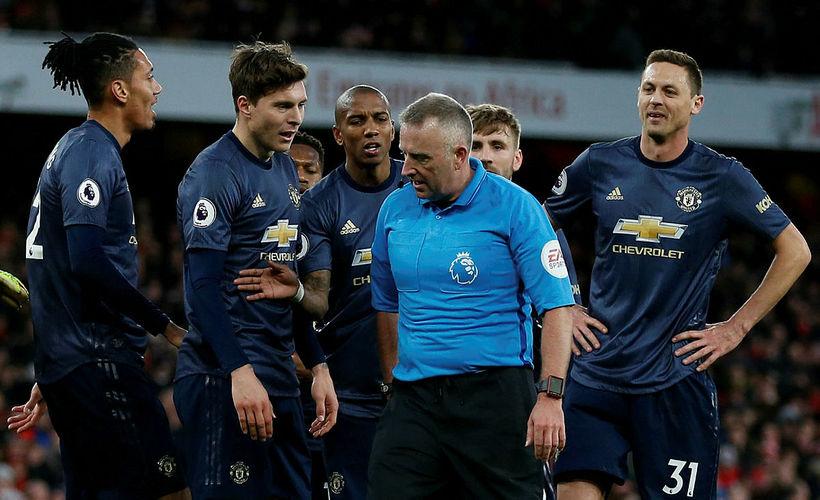 Dómarinn Jonathan Moss umkringdur leikmönnum Manchester United.