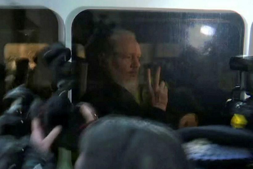 Julian Assange veifaði til fjölmiðlamanna úr aftursæti lögreglubíls, er honum …
