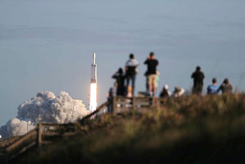 Áhorfendur fylgjast spenntir með þegar Falcon Heavy, kraftmestu geimflaug heims, ...