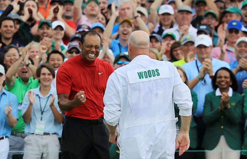 Tiger Woods fagnar með kylfusveini sínum.
