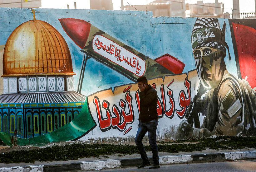 Palestínskur maður gengur fram hjá veggmynd í bænum Rafah á ...