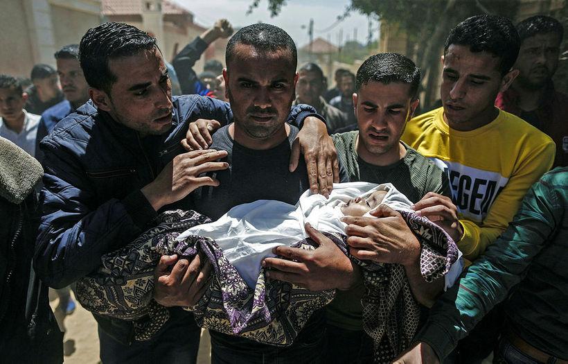 Syrgjendur í Gaza bera hér barn sem féll í árásum ...