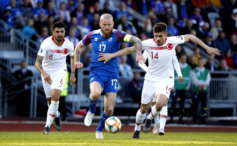 Aron Einar Gunnarsson and Dorukan Tokoz fight for the ball.