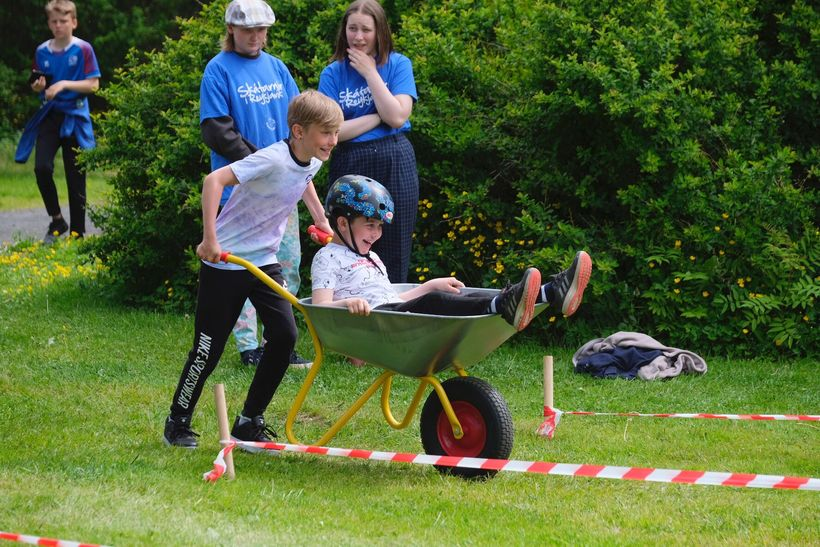 Children competed in a wheelbarrow race.