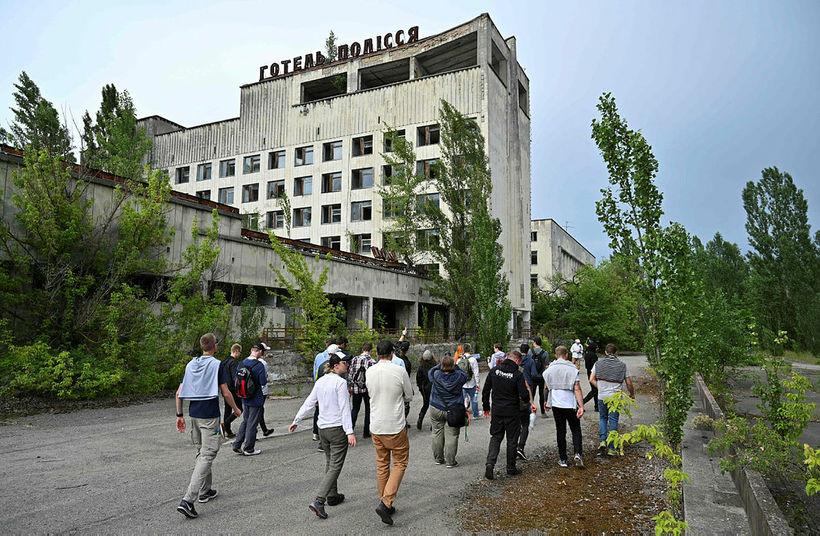 Ferðamenn ganga hér um draugaborgina Pripyat, í nágrenni Tsjernóbíl-kjarnorkuversins, sem …