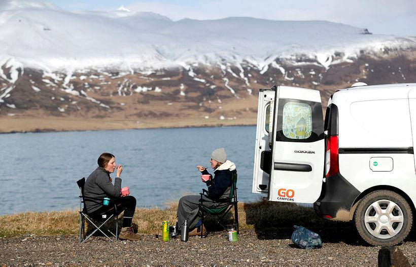 Ferðamenn njóta sín við Hafnarhólma í Borgarfirði eystra. Bílaleigubílum í ...