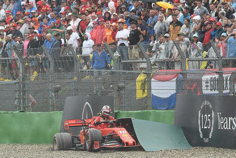Charles Leclerc klifrar upp úr Ferrarifáknum eftir skell á öryggisvegg.