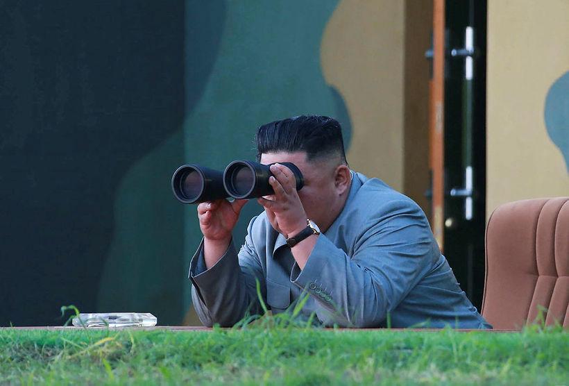 Kim Jong-un einræðisherra horfir með sjónauka á skammdræga eldflaug sem ...