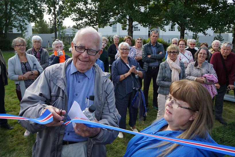 Jón Hallsson klippir á borðann, kampakátur.