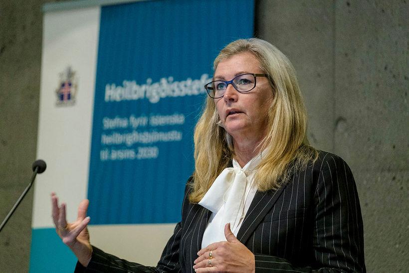 Alma Möller landlæknir árið 2019 í teinóttum jakkafatajakka og hvítri …