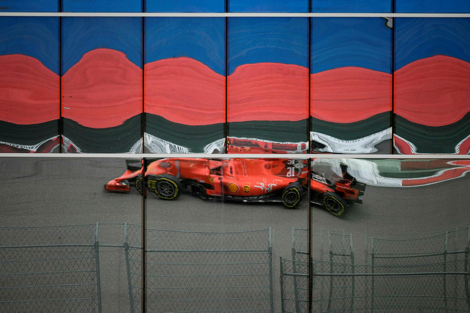 Ferrarifákur Charles Leclerc speglast í glerveggjum bygginga við brautina í ...