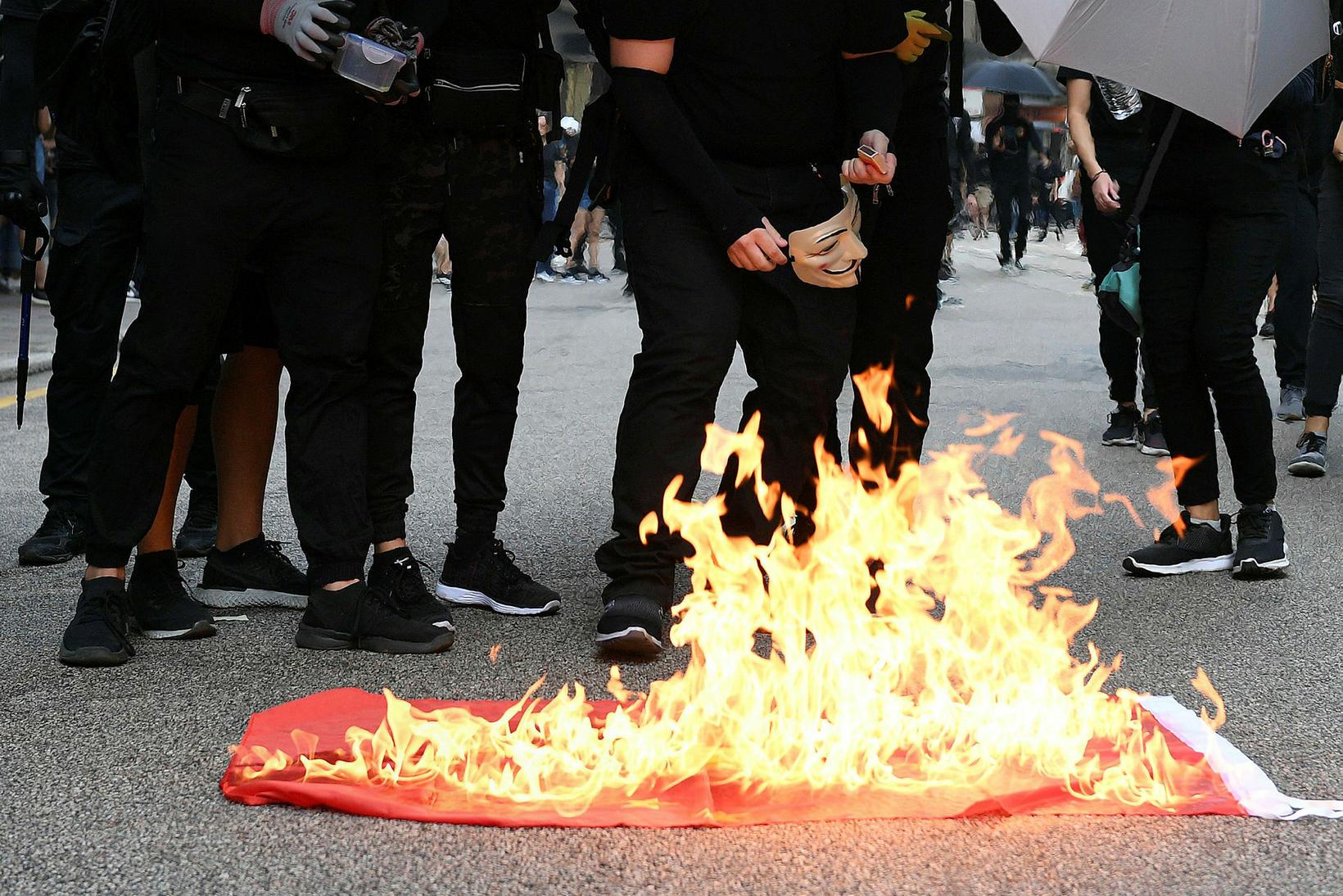Mótmælendur í Hong Kong brenna kínverska fánann.