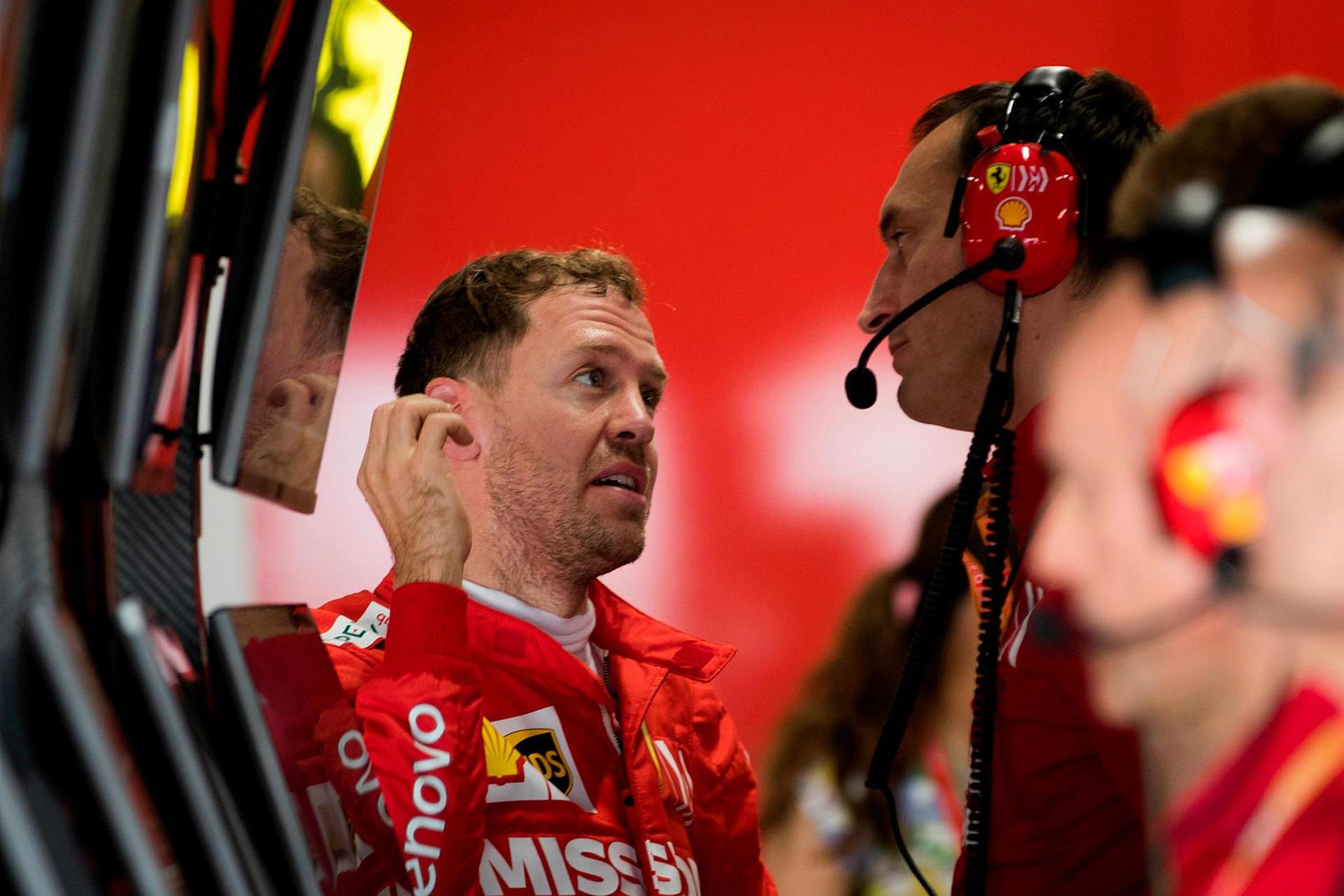 Sebastian Vettel ræðir við tæknimann hjá Ferrari eftir fyrri æfinguna ...