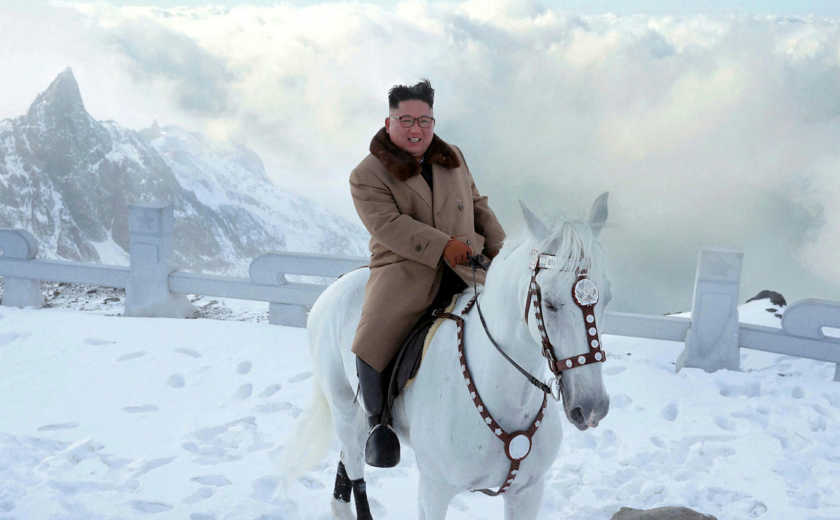 Kim Jong-un á hvítum hesti á snæviþaktri jörð.