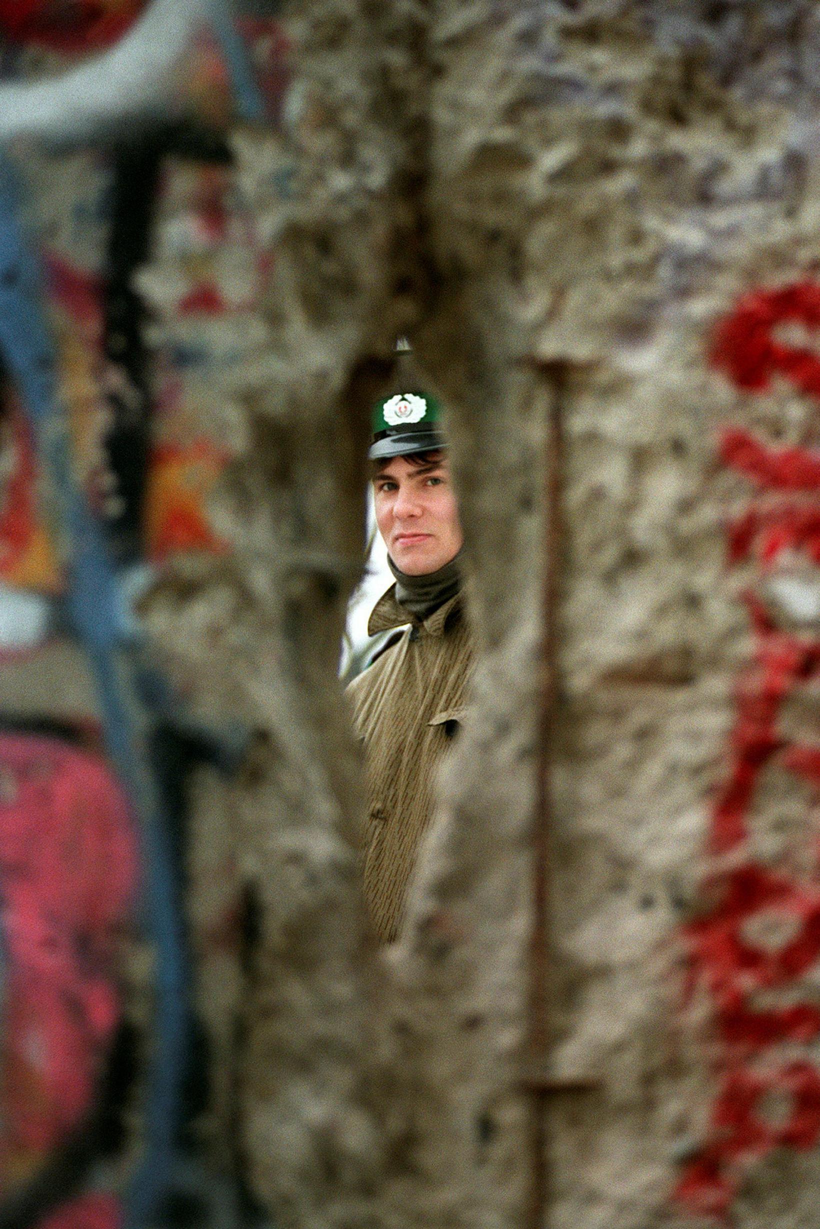 Austurþýskur hermaður gægist handan múrsins 1989, sem er þegar settur ...
