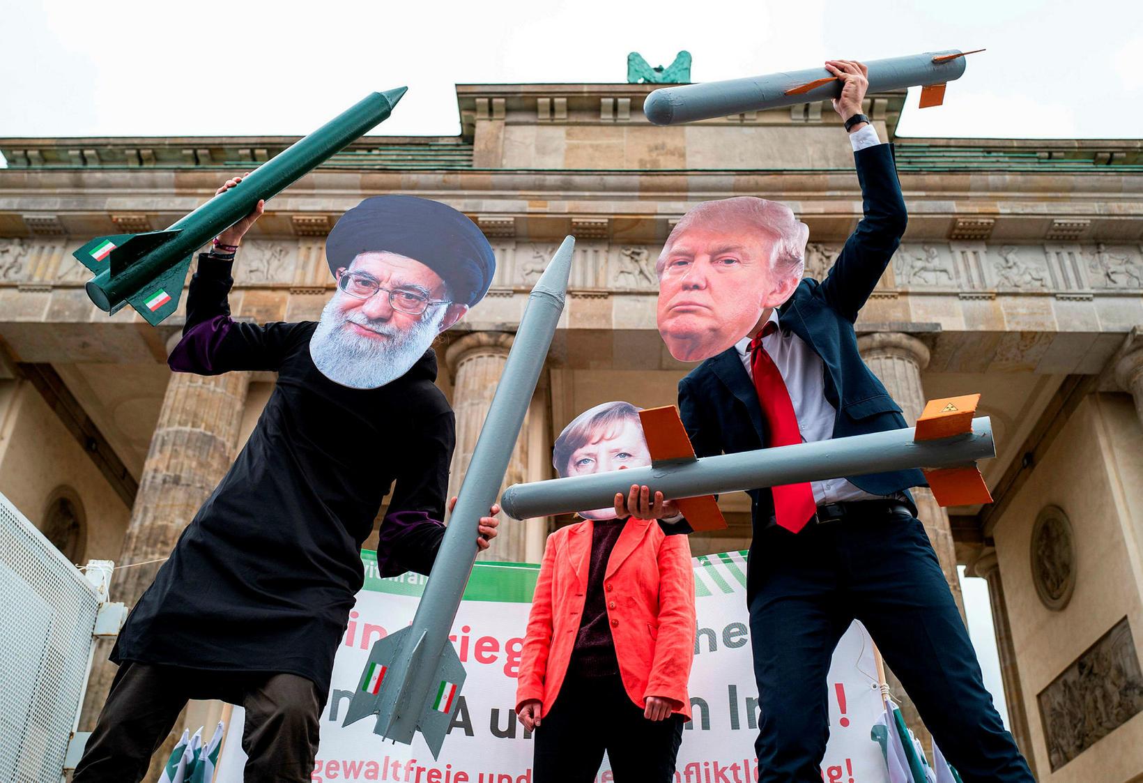 Hernaðarandstæðingar með grímur Ali Khamenei, Angelu Merkel, kanslara Þýskalands og …