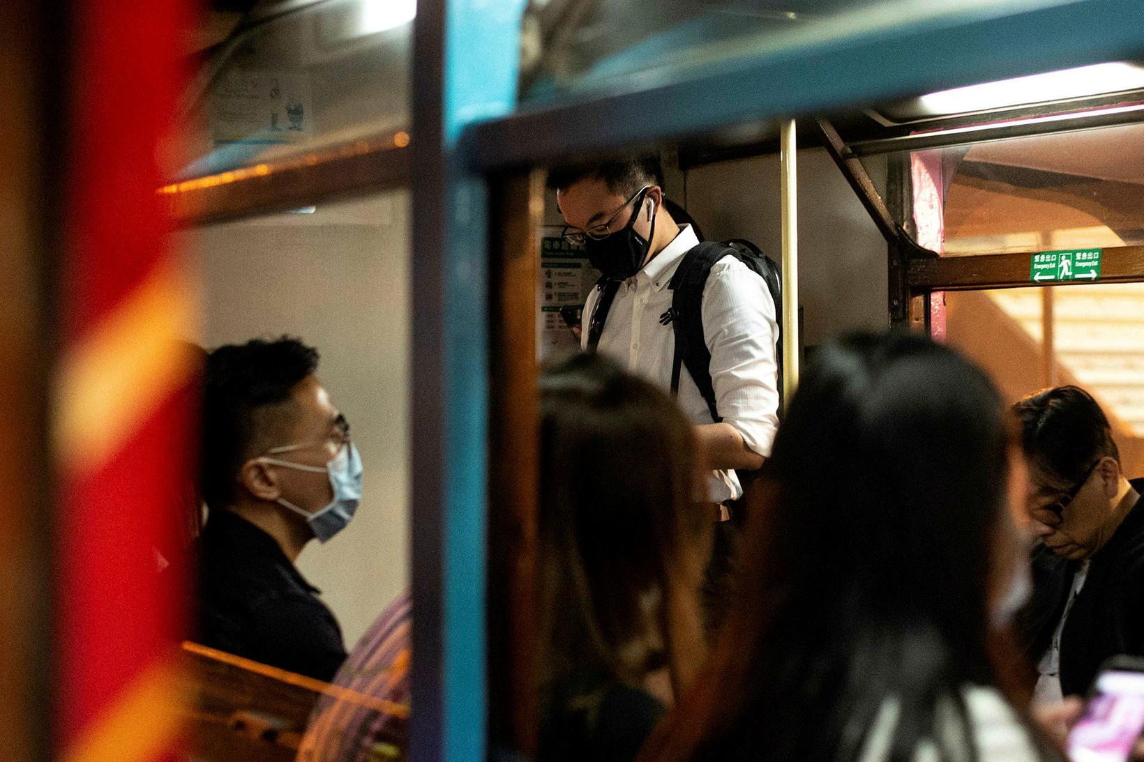Karlmenn með sóttvarnargrímur í lest í Hong Kong.