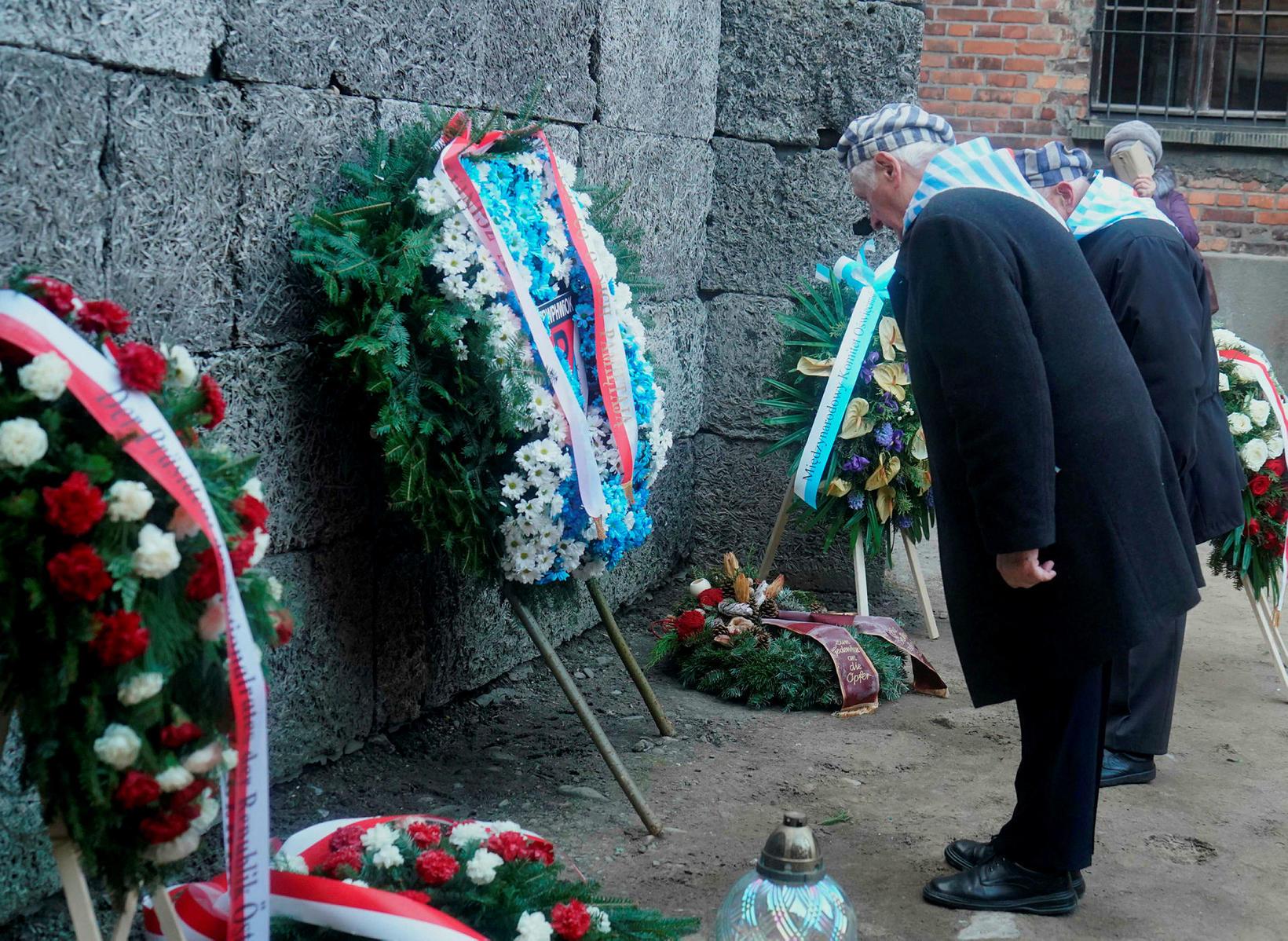 Blómsveigar voru lagðir við dauðavegginn í Auschwitz en þar var …