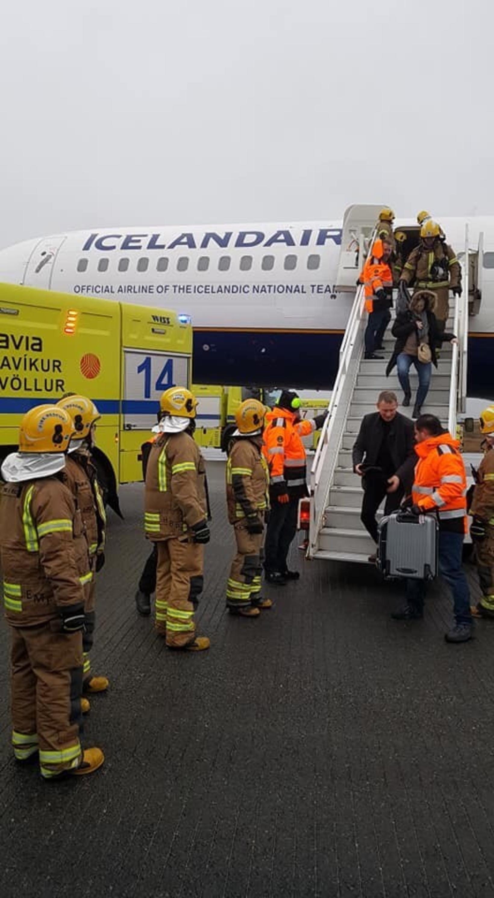First responders assist passengers in disembarking.