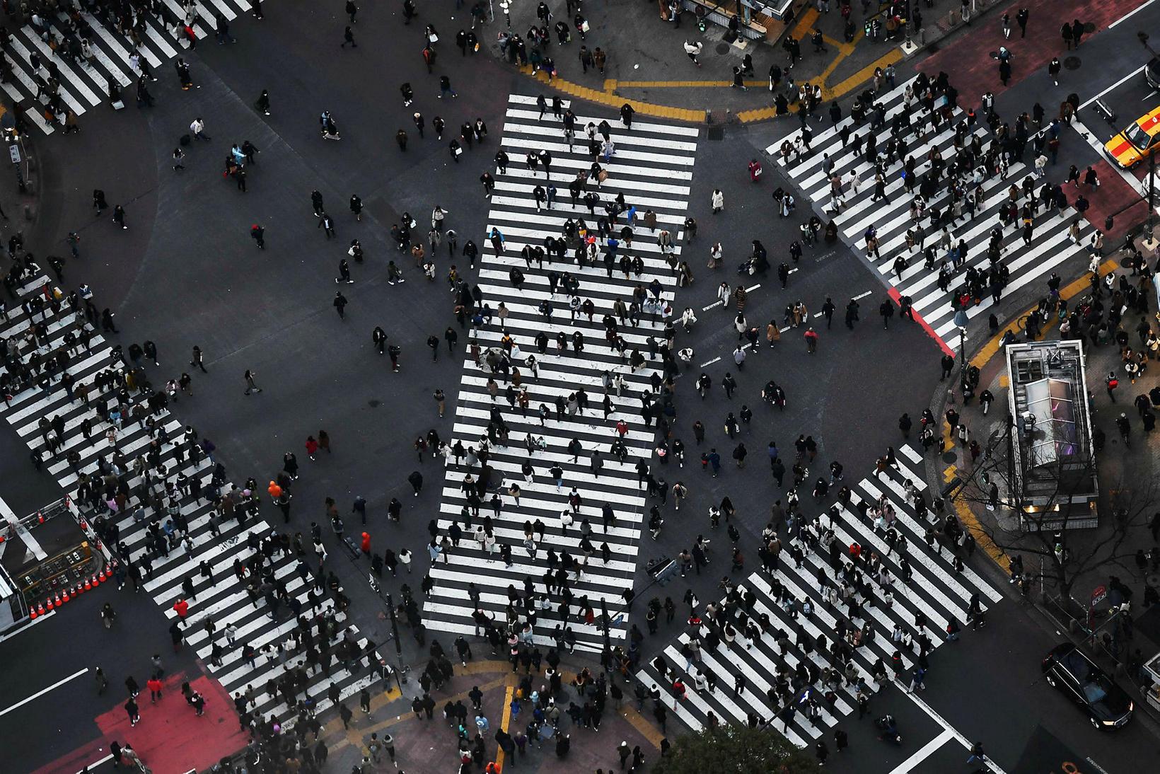 Hópur fólks gengur yfir gangbrautirnar frægu í Shibuya-hverfinu í Tókýó.