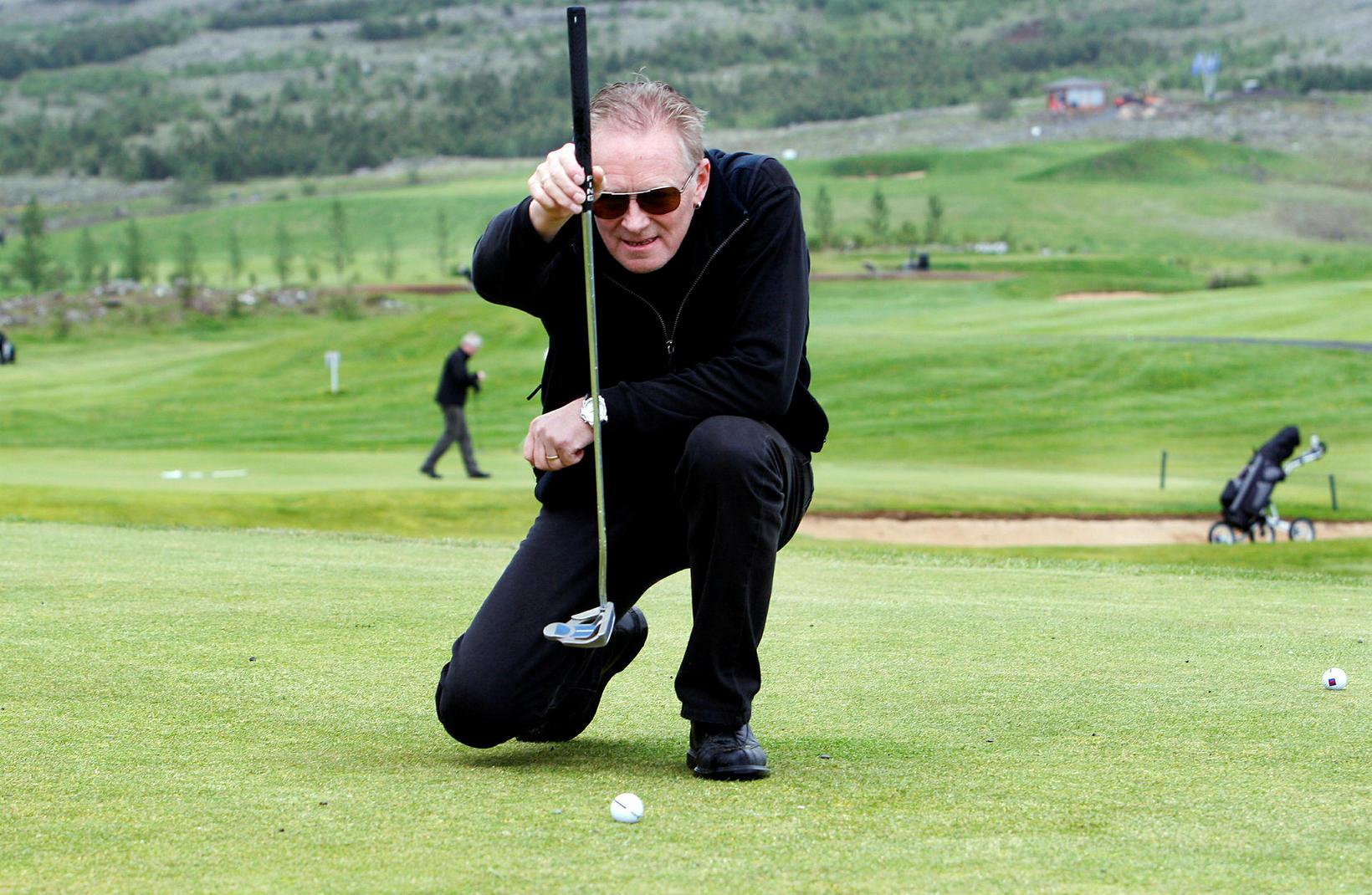 Laddi mælir fyrir pútti. Hann er illa haldinn af golfveirunni.