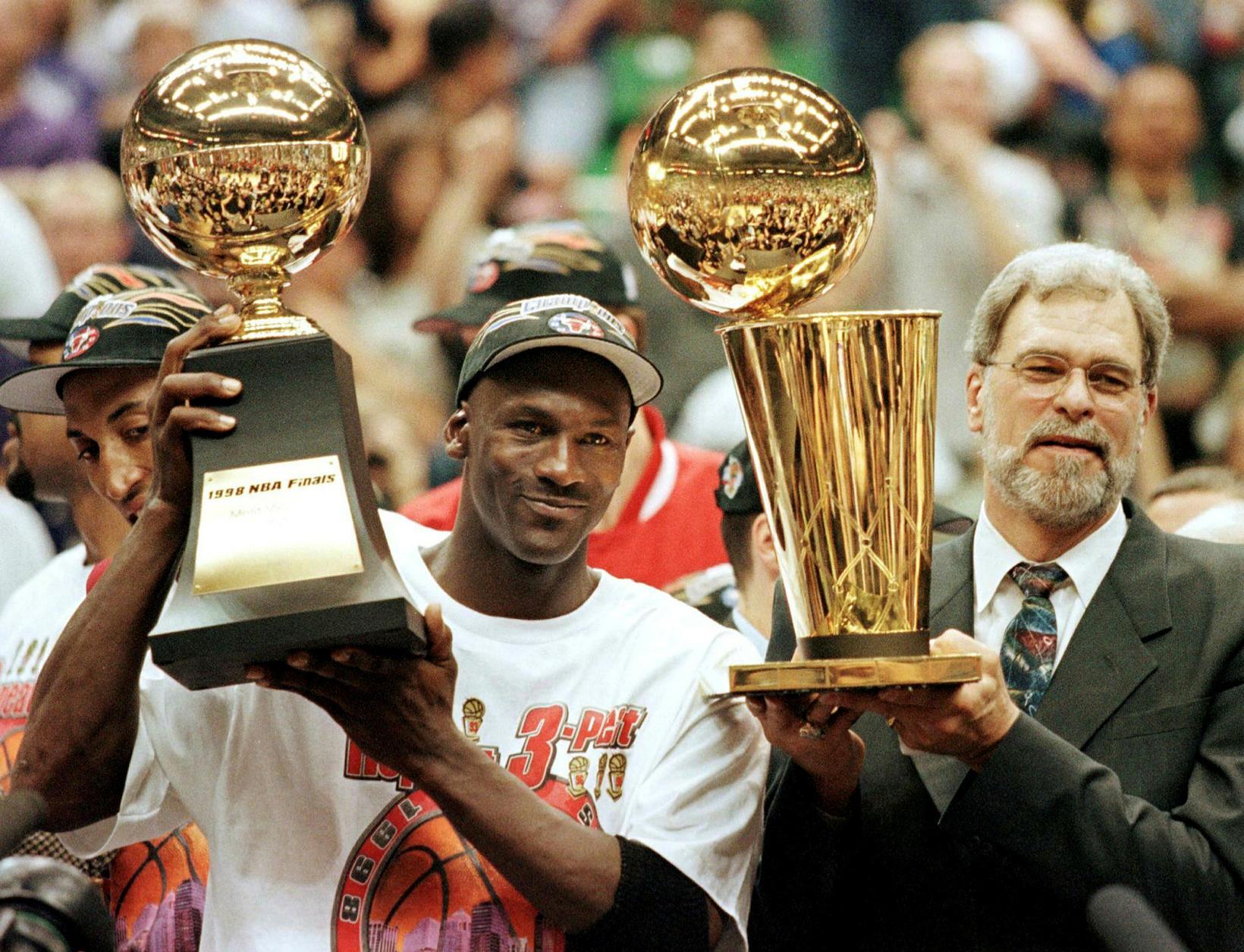 Michael Jordan og Phil Jackson fagna meistaratitlinum árið 1998 en …